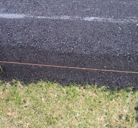 stakes pushed into driveway to mark paving progress