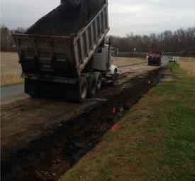 Paving crew using trucks to pave a road