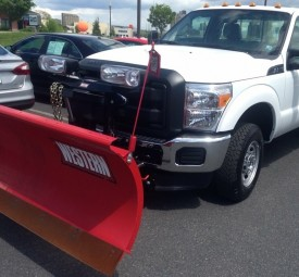 Closeup of large snow plow on front of pickup truck