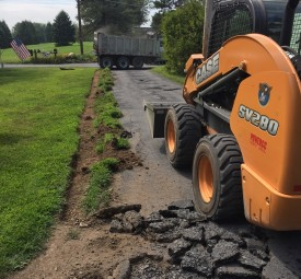 Skid steer being used to break up old driveway pavement
