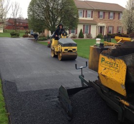 Crew using equipment to pave driveway