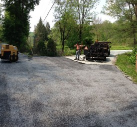 Crew performing tar chip paving for driveway