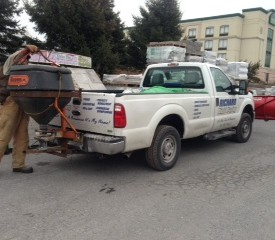 Man adding road salt to the deicer equipment on back of truck
