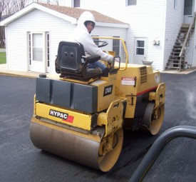 Paving crew using steam roller for driveway outside of house