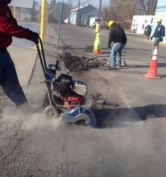 Paving crew using equipment to remove damaged pavement