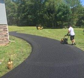 Crew sealing pavement on edges of driveway