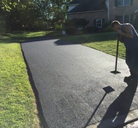 Crew using tool to flatten imperfections of paved driveway by hand