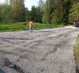 Crew laying down tar chip for private property driveway in the woods