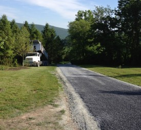 Crew paving residential driveway in woods