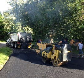 Paving crew using steamroller to even driveway after paving