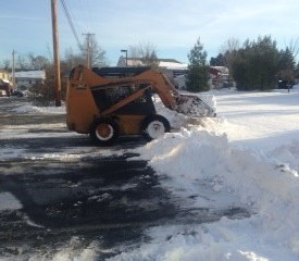 Crew using skid steer to plow snow at Creekside senior community